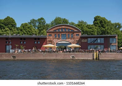 LUBECK, GERMANY - MAY 25, 2018: cafe with guests on the bank of the trave river in lubeck, germany