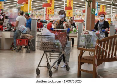 LUBIN, POLAND - APRIL 9, 2020. Women customers with face mask and trolleyes after shopping in Auchan supermarket.