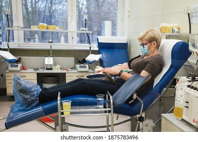 LUBIN, POLAND - DECEMBER 9, 2020. The woman with face mask donates blood plasma at the donation center. Plasma from convalescents is used to treat patients with Covid-19 disease.