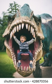LUBIN, POLAND - MAY 25, 2016 - Boy seating in the mouth of model dinosaur Tyranosaurus Rex in Park Wroclawski. Park is well known tourist attraction for children in this region of Poland.