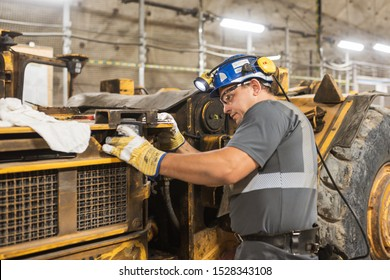 LUBIN, POLAND - OCTOBER 10, 2019 : Blue color worker repairs loading machine in copper mine that belongs to KGHM Polska Miedz.
