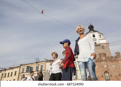 LUBLIN - JULY 28: Man practicing highline in Lublin during Urban High Line festival. Highline is a balance sport that consists walking through a rope clamped between two points and great height below.