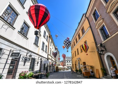 Lublin, Poland - August 10, 2017: Mountebanks Carnaval in Lublin old town, Poland. Beautiful street and old bright buildings in the old town of Lublin. Brama street, view on Cracow gate, Lublin.