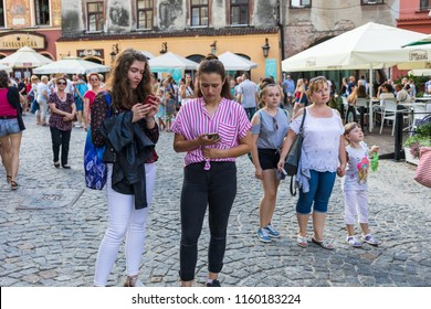 Lublin, Poland - Jul 27, 2018: Crowds of tourists and holidaymakers on the streets of the old city of Lublin. Two young girls with smartphones. Lublin is the ninth largest city in Poland
