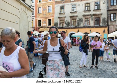 Lublin, Poland - Jul 27, 2018: Crowds of tourists and holidaymakers on the streets of the old city of Lublin. Young woman with self-stick and smartphone. Lublin is the ninth largest city in Poland