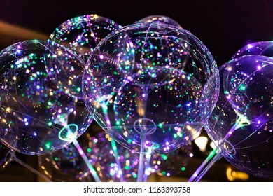 Lublin, Poland - Jul 27, 2018: LED transparent balloon with multi-colored luminous garland. Vivid lights at night. Illuminated balloons on the streets of Lublin