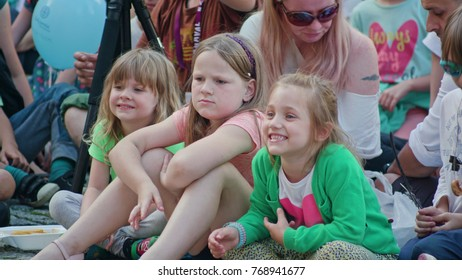 Lublin, Poland - July 2017: Kids are sitting on the pavement, laughing and watching Mattatoio Sospeso's aerial dance and clown show Out during Festival Sztukmistrzow. Girls and a woman are eating