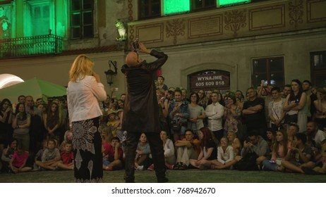 Lublin, Poland - July 2017: Krystian Minda Sword Swallower Show in Lublin at night, during Festival Sztukmistrzow. Crowd stays and sits on the pavement, and watches the show with amazement. Medium