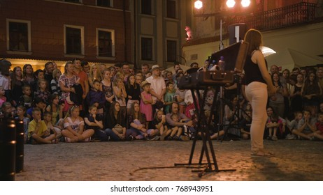 Lublin, Poland - July 2017: Krystian Minda Sword Swallower Show in Lublin at night, during Festival Sztukmistrzow. Kneels in front of his assistant. The tool box on the first plan i out of focuse