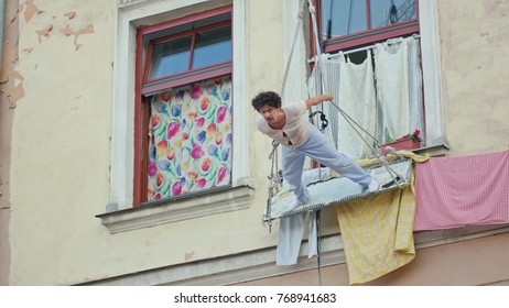Lublin, Poland - July 2017: Mattatoio Sospeso performes aerial dance and clown show Out during Festival Sztukmistrzow. Dances on the boards suspended on ropes opposite the windows. Sunny. Afternoon