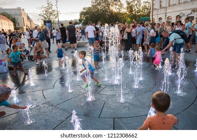 LUBLIN, POLAND - JULY 27, 2018: : Happy children playing in a water fountain in a hot day in Lublin. Lublin is the ninth largest city in Poland
