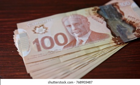 Lublin, Poland - September 2017: Fanned pile of Canadian hundred dollar banknotes on a table. Close-up shot