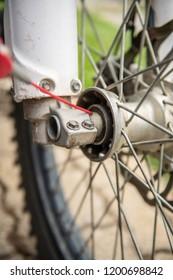 Lubricating motorcycle wheel bearings with dedicated chain spray grease.