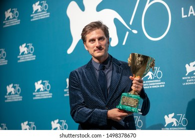 """Luca Marinelli poses withthe Coppa Volpi for Best Actor Award for """"Martin Eden"""" at the Winners Photocall during the 76th Venice Film Festival at Sala Grande on September 07, 2019 in Venice, Italy."""