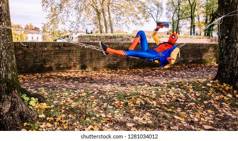 Lucca, Italy, 03/11/2018: Cosplayer dress by Spider Man performs in the park of Lucca during carnival festivities