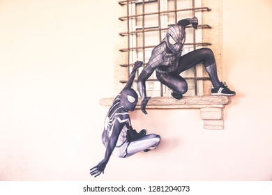 Lucca, Italy, 03/11/2018: Two cosplayers disguised as Spider Man perform climbing on the walls during the carnival party in Lucca