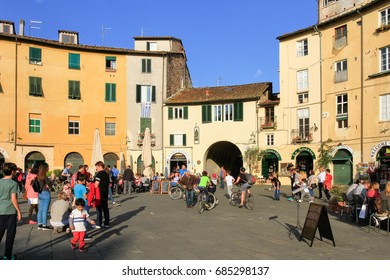 Lucca, Italy - April 09, 2017: People walking during a sunny day in Piazza Anfiteatro in the center of Lucca.