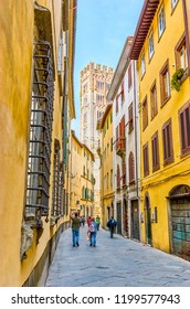 LUCCA, ITALY - APRIL 30, 2013: The narrow streets in Lucca attract tourists wishing to enjoy Italian atmosphere, on April 30 in Lucca
