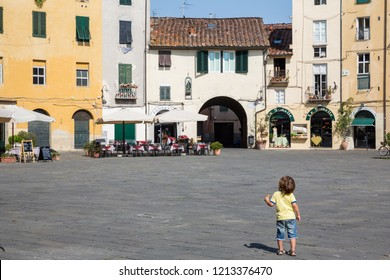 Lucca Italy July 4th 2015 : Young child with ice cream cone in  Piazza dell'Anfiteatro which is a public square in the northeast quadrant of walled center of Lucca, region of Tuscany, Italy