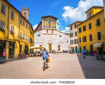 LUCCA, ITALY - JUNE 18, 2015:  Tourists bike in urban Piazza San Frediano in the historic centre of Lucca, Italy city