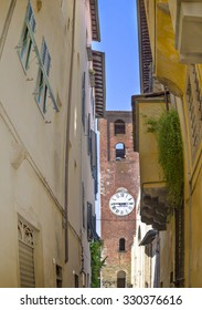 LUCCA, ITALY - JUNE 25, 2015. Narrow street  with  antique Clock Tower in Lucca , Puccini 's home town.