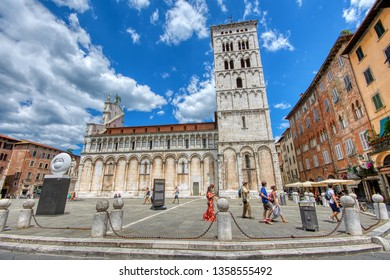 Lucca, Italy - June 26, 2018: View of medieval cathedral San Michele in Lucca, Italy. Tourists walking through the historic center of Lucca.