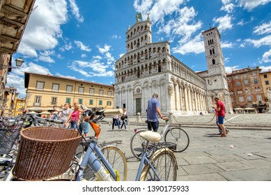 Lucca, Italy - June 26, 2018: View of medieval cathedral San Michele in Lucca, Italy. Tourists walking and cycling through the historic center of Lucca.