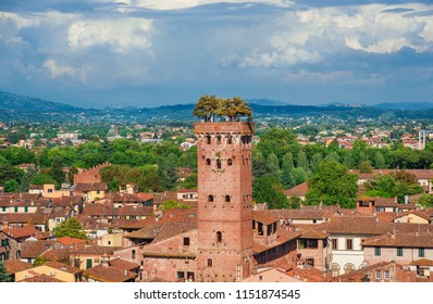 LUCCA, ITALY - MAY 10, 2018: The famous and characteristic medieval Guinigi Tower with oak trees and tourists at the top, erected in the 14th century in the historic city center
