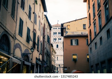 Lucca, Italy, September 14, 2018: Bell tower of Chiesa di San Michele in Foro catholic church view through narrow street in historical centre of old medieval town, evening view, Tuscany