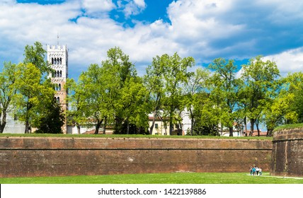 Lucca, Tuscany / Italy - April 18th, 2019: Outside the walls of Lucca with some guys leaving the city and the bell tower of the Duomo di San Martino