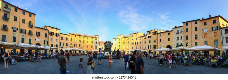 Lucca, Tuscany / Italy - August 2017: Peoples walking in a rounded square of Lucca city, panoramic view