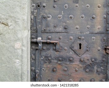 Lucca, Tuscany, Italy, May 22, 2019. Old iron door set in stone.  Metal studs, bolt and keyhole. Just off Piazza San Martino.  Lucca, Tuscany, Italy, May 22, 2019.