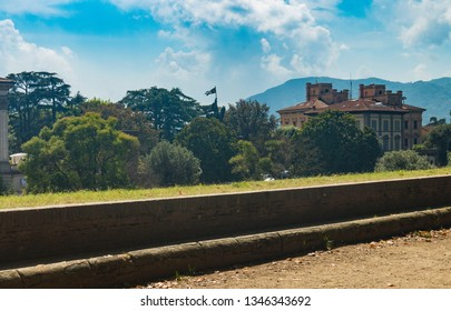 """Lucca, Tuscany, September, 2018. City walls of Lucca. View at the Monument  """"la Patria Vincitrice"""" (to the citizens of Lucca fallen in wars for independence of Italy)."""