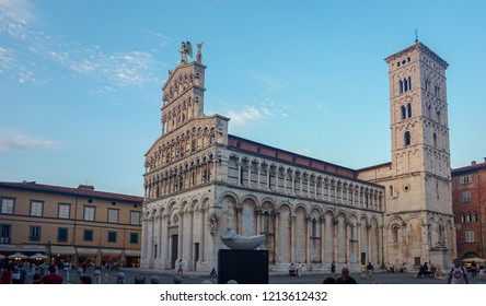 Lucca, Tuscany, September, 2018. View at  St Michael Church, (Chiesa di San Michele in Foro) with contemporary sculpture on the foreground.