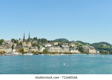 LUCERNE - August 18: A swan swims on Lake Lucerne with grand buildings in the background August 18, 2017 in Lucerne, Switzerland.