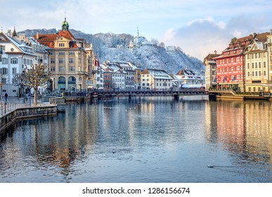 Lucerne city, Switzerland, view of the Old Town covered with white snow in winter, reflecting in the river