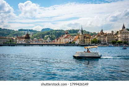 Lucerne Switzerland , 28 June 2020 : Tourists on a license free boat to rent on Lucerne lake and city with landmarks such as chapel bridge in background in Lucerne old town Switzerland