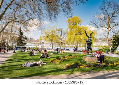 LUCERNE, SWITZERLAND- APRIL 19, 2019: People relaxing at Inseli park Lucerne, enyoing the spring sun.
