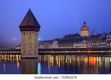 "LUCERNE, SWITZERLAND -  December 18, 2016. The famous Kapellbrucke (literally ""Chapel Bridge""), a footbridge over Reuss River. To the left you can see  the ""Wasserturm"" (literally ""water tower"")   - Shutterstock ID 713954179"