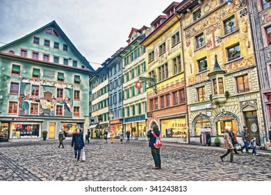 LUCERNE, SWITZERLAND - JANUARY 04, 2015: Historical buildings with frescos on the right bank of the River Reuss at picturesque square Muhlenplatz in Lucerne, Switzerland