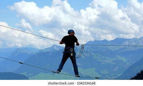 Lucerne, Switzerland - July 22, 2017: Man in a rope park with the Alps in the background