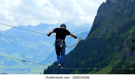 Lucerne, Switzerland - July 22, 2017: Careful balancing of a man on a rope in the climbing park with the Alps in the background