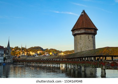 Lucerne, Switzerland- October 7, 2019: The Chapel Bridge reflecting upon Lake Lucerene can be seen at dusk.