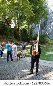 Lucerne/Switzerland - August 21 2015: A traditional alphorn player in Löwendenkmal, Lucerne. Lucerne is the capital of the Canton of Lucerne and the capital of the district of the same name.
