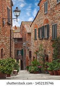 Lucignano, Arezzo, Tuscany, Italy: picturesque narrow alley with plants and flowers in the ancient Tuscan town