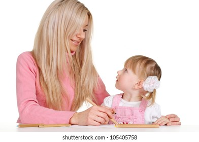 A luck Caucasian mother with her daughter paint crayons on a white background