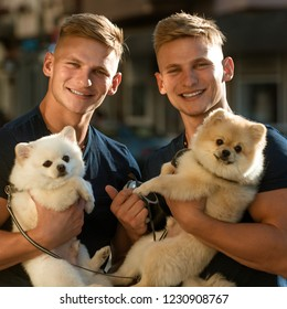 Lucky to be together. Twins men hold pedigree dogs. Happy twins with muscular look. Muscular men with dog pets. Spitz dogs love the company of their family. Happy family on walk.