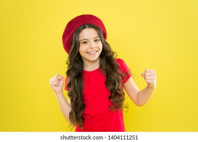 Lucky and beautiful. Kid girl long healthy shiny hair wear red hat. Little girl with long hair. Kid happy cute face adorable curly hair yellow background. Beauty tips for tidy hair. Smiling child.