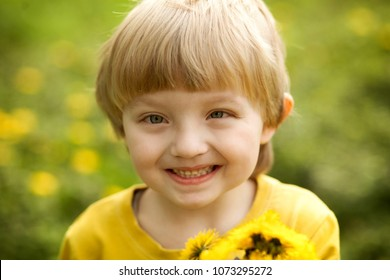 lucky boy blond four (4) years with the squint sitting in a field of dandelions and smiling, a child on a background of green grass, holding a dandelion yellow