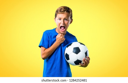 Lucky boy playing soccer on yellow background